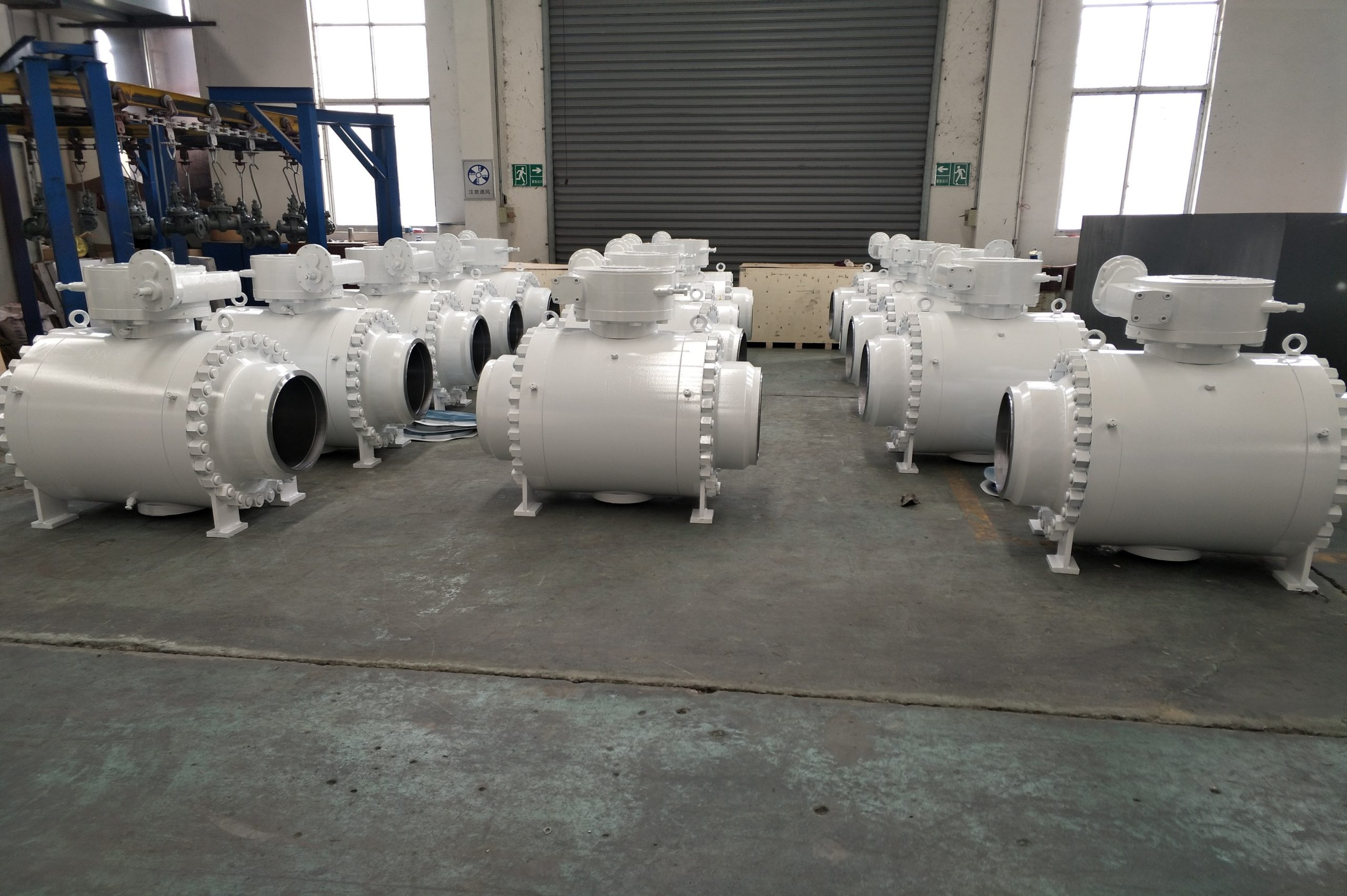 Three rows of white coloured ball valves arranged at a workshop by an industrial valve manufacturer in india